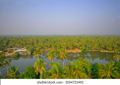 Aerial view of Parvathy Puthanaar canal surrounded by coconut trees in Anchuthengu, a coastal town in the Thiruvananthapuram District.