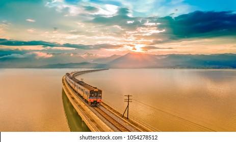 Aerial view, Passenger tourist train above the lake of Pa Sak Jolasid dam at Lopburi unseen Thailand  during beautiful sunset. Amazing Thailand Train run on the bridge look like floating on the water
