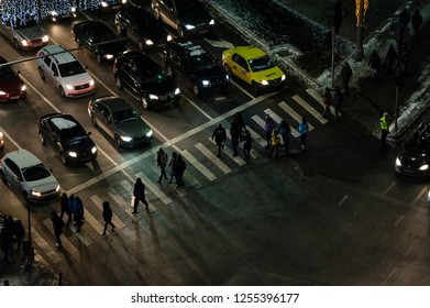 Aerial view of a pedestrian crossing in Victoriei Square evening traffic . Bucharest, Romania, December 1,2018.