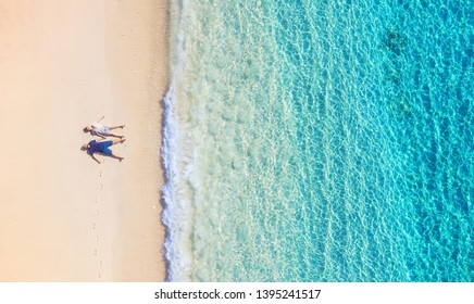 Aerial view of a people couple on the beach on Bali, Indonesia. Vacation and adventure. Beach and turquoise water. Top view from drone at beach, azure sea and relax couple. Travel and relax - image