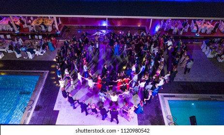 Aerial view of people dancing on a wedding. Top view of balkan dance on a wedding night by the pool