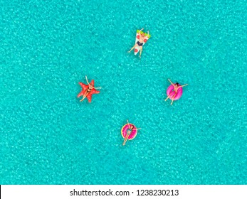 Aerial view of people floating on inflatable pizza, flamingo, star and donut shaped mattresses, relaxing.