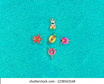 Aerial view of people floating on inflatable pizza, flamingo, star, pineapple and donut shaped mattresses, in formation.