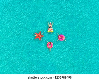 Aerial view of people floating on inflatable pizza, flamingo, star and donut shaped mattresses, joining hands.