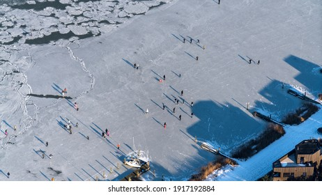 Aerial view of people having fun and ice skating on a frozen IJ in Amsterdam IJburg.
