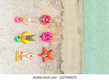 Aerial view of people lying on inflatable pineapple, pizza, star, donut, flamingo shaped mattresses on beach.