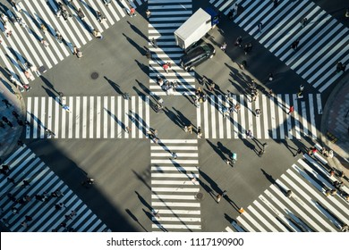 Aerial view of people passing crosswalk in the downtown street.