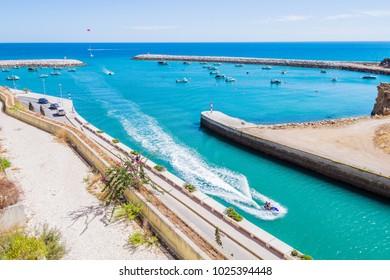 Aerial view of people riding a jet powered boat in Porto de Abrigo de Albufeira, Albufeira Bay in Albufeira, Portugal