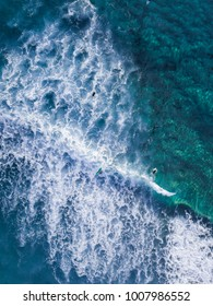 Aerial view of people surfing the wave.