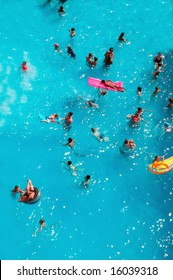 Aerial view of people swimming in pool while on holiday.