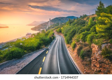 Aerial view of perfect mountain road and beautiful green forest at colorful sunset in summer. Dubrovnik, Croatia. Top view of road, sea, mountain, sky. Landscape with highway, sea coast, gold sunlight