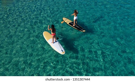 Aerial view photo of 2 unidentified attractive fit young women practising stand up paddle board or SUP in tropical caribbean sapphire crystal clear sandy exotic beach