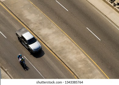 Aerial view of a pick up truck and motorbike on an empty road