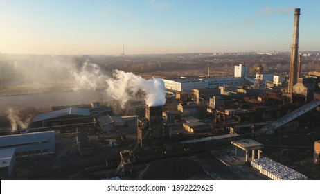 Aerial view pillar of smoke emitting from plant pipes. Drone flying above industry zone pouring toxic vapors in air. Beautiful landscape at background. Nature pollution problem. Slow motion Top view.