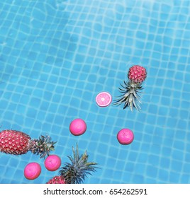 Aerial view of pineapple and oranges floating in swimming pool