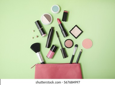 Aerial view of a pink leather make up bag with cosmetic beauty products spilling out on to a pastel green background