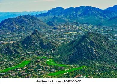 Aerial view of Pinnacle Peak, McDowell Sonoran Preserve, multiple Troon Golf course fairways, and overhead views of residential neighborhoods in Troon Village in Scottsdale, Arizona USA