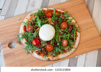 Aerial view of a pizza on a wooden board with cherry tomatoes, arugula, and burrata cheese on a wooden table