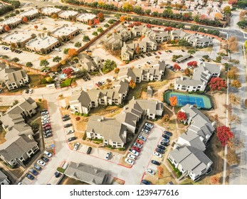 Aerial view  planned unit development with community tennis court in Dallas suburb of Irving, Texas, USA. Colorful fall foliage leaves, row of single-family homes, urban sprawl subdivision