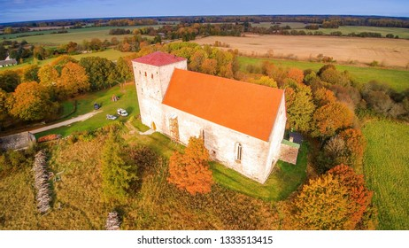 Aerial view of the Poide church in Saaremaa. It is on a hill being surrounded with green grass fields