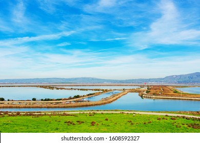 Aerial view of ponds and levees in San Francisco Bay under blue sky. Background San Francisco Bay and Diablo Mountain Range.