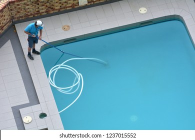 Aerial view of a pool cleaner cleaning a pool. Real people. Copy space