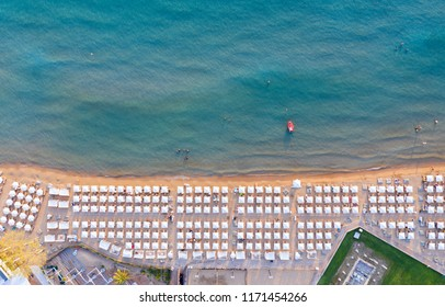 Aerial view to the popular Astir Beach in Vouliagmeni, Athens, Greece, with symmetrical placed sunbeds and umbrellas