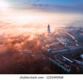 Aerial view of the popular tourist place of Kiev-Pechersk Lavra in Kiev at dawn in the fall with the city in the background covered with fog and birds flying to the south.