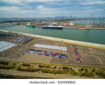 Aerial view of Port Melbourne with moored cargo vessels, imported cars parking lots, and Melbourne CBD skyline on the horizon