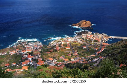 Aerial view of Porto Moniz harbor. Nice village with heliport, harbor and natural volcanic sea pools. Madeira island, Portugal.