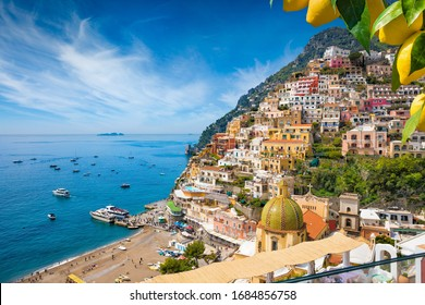 Aerial view of Positano with comfortable beach and blue sea on Amalfi Coast in Campania, Italy. Amalfi coast is popular travel and holyday destination in Europe. Ripe yellow lemons in foreground. - Shutterstock ID 1684856758