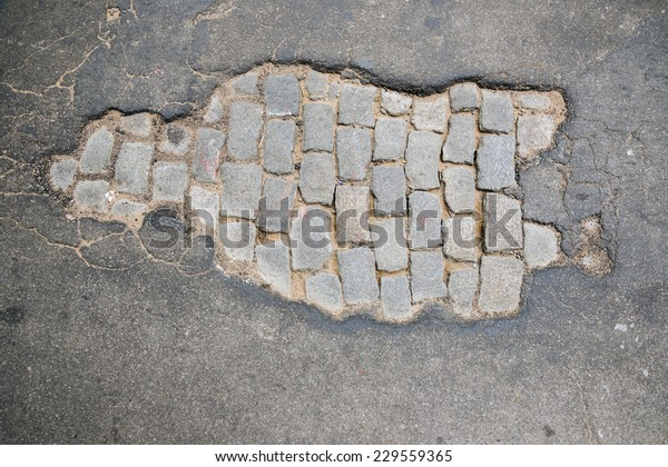 Aerial view of a pothole in an asphalted road that let exposed the antique paving in Rosario city, Argentina