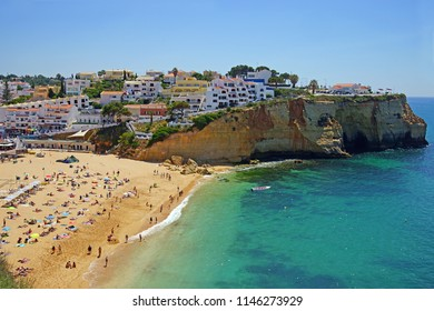 An aerial view of Praia da Cavoeiro and the turquoise sea with many holiday makers enjoying the summer sun, The Algarve, Portugal