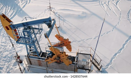 aerial view of pumpjack on oil well in snowy field in winter day, camera is moving around, extraction of petroleum