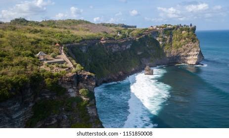 Aerial view at Pura Luhur Uluwatu temple. Stone cliffs, ocean waves and ocean landscape. Bali island, Indonesia.