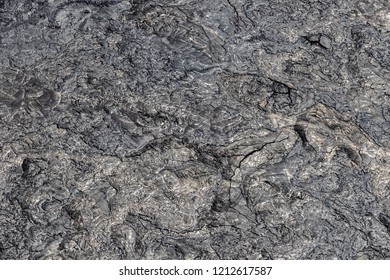 Aerial view of Puu Ooo Volcanic pahoehoe lava field from recent eruption. The surface is swirled and wrinkled; it's smooth metalic surface reflecting silver. Giant cracks from cooling.