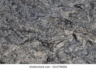 Aerial view of Puu Ooo Volcanic lava field. The pahoehoe lava's surface is swirled and wrinkled; it's smooth metallic surface reflects silver. Giant cracks from cooling. On Hawaii's Big Island.