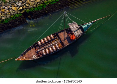 Aerial view of Rabelo Boat with barrels of Port wine on river Douro. Traditional Portugese sailing Vessel loaded with vine casks. Porto, Portugal.