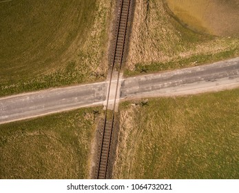 aerial view of railroad tracks crossing a country road in rural area in germany
