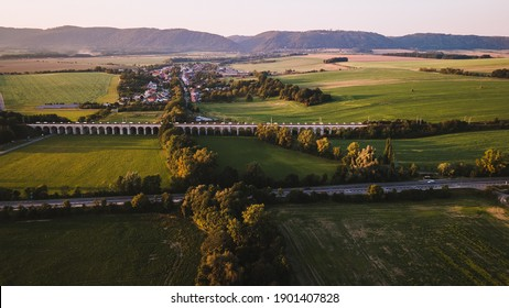 Aerial view of a railway viaduct with a car path near Lipnik nad Becvou with the surrounding countryside and a village nearby during the late afternoon.