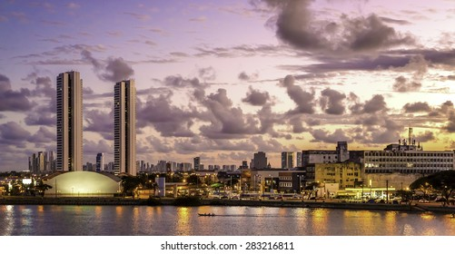 Aerial view of Recife in Pernambuco, Brazil showcasing its mix of historic architecture with buildings dated from the 17th century and modern skyscrapers at sunset.