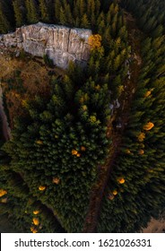 Aerial view of the Recreation Mountain Pysany kamin in Carpathian mountains. autumn. Pine forest, houses on the peaks, yellow fields and trees. Mountain meadow. sunset, vertical photo. Ukraine