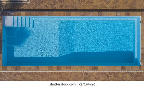 Aerial view of a rectangular swimming pool belonging to a large villa. The water is transparent and through the blue you can see the steps. Around The water there is a red tile floor.