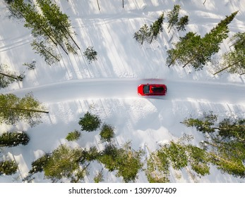 Aerial view of red car driving through the white snow winter forest on country road in Finland, Lapland. Top view from drone