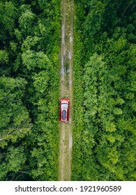 Aerial view of red car with a roof rack on a green summer forest country road in Finland