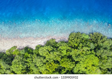 Aerial view of reef and rainforest in Papua New Guinea. The remote, tropical islands in this region are home to extraordinary marine biodiversity and are part of the Coral Triangle.