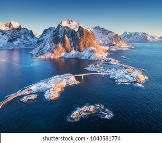 Aerial view of Reine and Hamnoy at sunrise in winter. Lofoten islands, Norway. Panoramic landscape with blue sea, snowy mountains, rocks, village, rorbuer, road, bridge, sky. Top view from drone