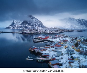 Aerial view of Reine in overcast day in winter in Lofoten islands, Norway. Moody landscape with blue sea, snowy mountains in low clouds, rocks, village, buildings, rorbu, cloudy sky. Top view. Travel