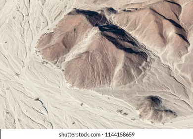 Aerial view of the relief of the desert and the lines of Nazca, the astronaut, Peru