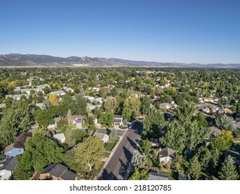 aerial view of residential area in Fort Collins, Colorado, with foothills of Rocky Mountains  in background from a low flying drone, late summer